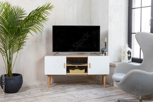 Fotografia, Obraz  TV in the interior in loft style on the bedside table with decorative items