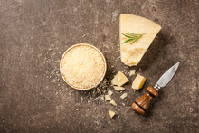 Sliced And Grated Parmesan Cheese On Stone Table