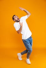 Full Length Image Of Frightened Guy 30s In T-shirt And Jeans Raising Hands While Standing, Isolated Over Yellow Background