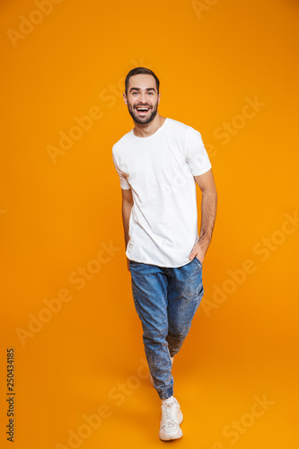 Full length photo of adorable guy 30s in t-shirt and jeans smiling while standing, isolated over yellow background Wall mural