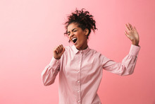 Beautiful Young African Woman Posing Isolated Over Pink Wall Background Screaming Singing.