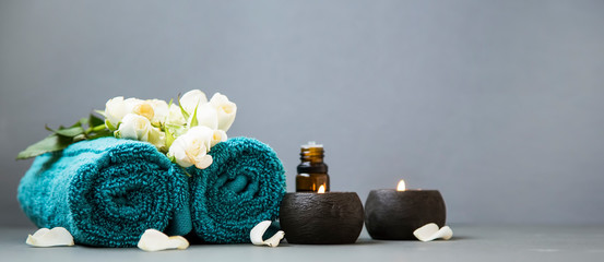 Spa still life with candles, towels and flowers on grey background copy space