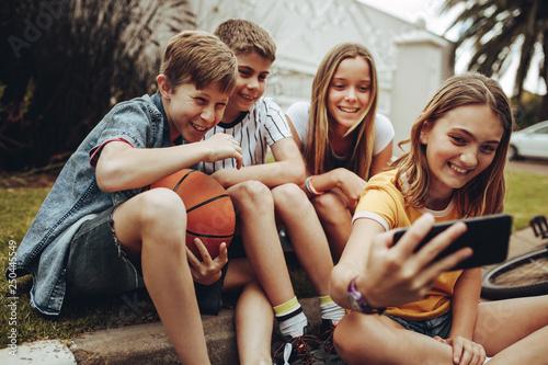 Fotografiet  Kids taking a selfie sitting outdoors