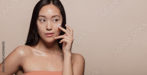 Photo Woman applying beauty product on face