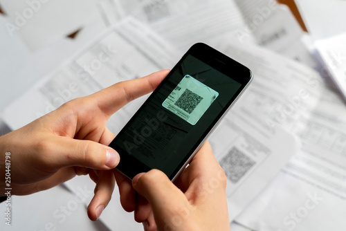 Valokuva  persons hand hold spartphone scanning qr code b