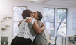 canvas print picture - Two female black african freelancers embraced in a friendly hug in a modern co-working space