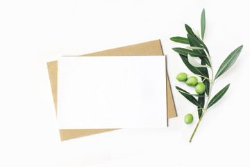 Feminine stationery, desktop mock-up scene. Blank horizontal greeting card and craft envelope with olive branch.White table background. Flat lay, top view.