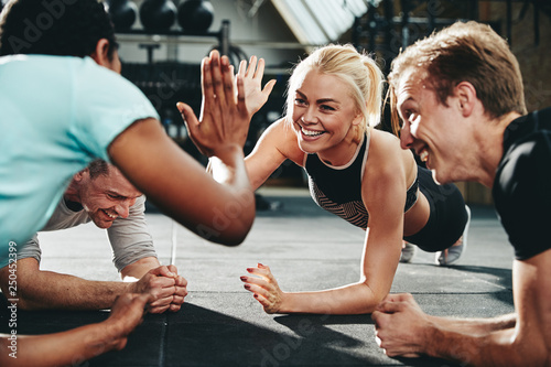 Two friends high fiving while planking on a gym floor