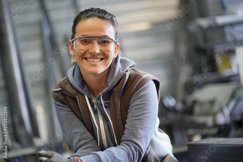 Fotografía  Woman apprentice training in metalwork workshop