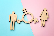 Female And Male Figures With Symbol Of Transgender On Color Background