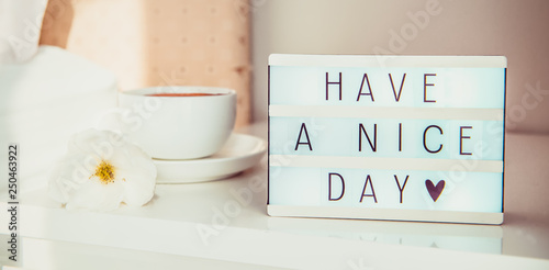 Fotografia  Close up Have a nice day text message on lighted box, cup of coffee and white flower on the bedside table in sun light