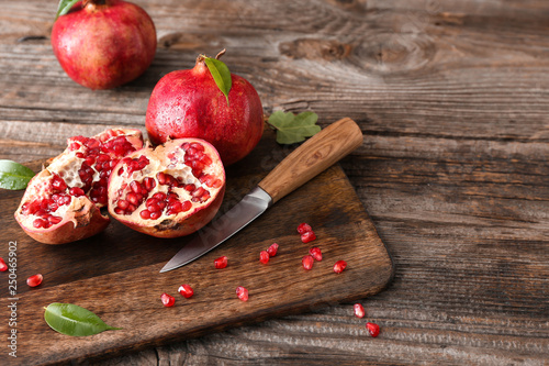Cutting board with ripe pomegranates and knife on wooden table