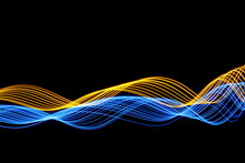 Long Exposure, Light Painting Photography.  Abstract Blue And Gold Waves And Ripples Pattern, Vibrant Duo Color Against A Black Background