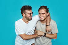 Image Of Ttwo Cheerful Handsome Guys Embracing Each Other, Wearing Casual Clothes, Isolated Over Blue Studio Background
