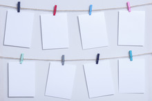 Blank White Cards Hanging On Colored Clothespins On A Thread On A White Background, A Template For A Photo Collage, A Concept Of Memories And A Photo Industry