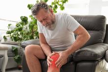 Senior Man Suffering From Knee Pain Indoors