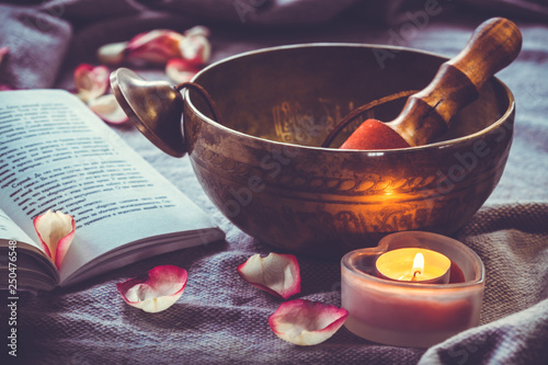 Photo  Tibetan singing bowl with book candel and rose petal