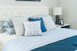 beach blue pillow on bed with side table lamp in bedroom