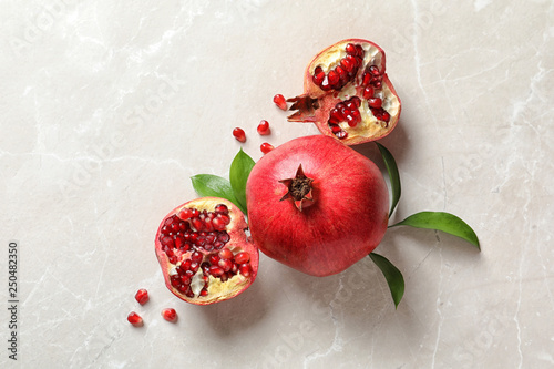 Flat lay composition with ripe pomegranates on light background