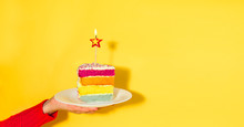 Female Hand Holding White Plate With Slice Of Rainbow Cake With Birning Candle In The Shape Of Star Isolated On Yellow Background. Happy Bithday, Party Concept. Wide Banner. Copy Space.