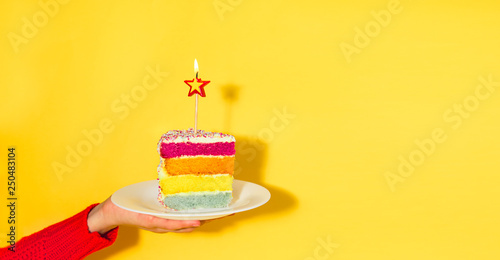 Female hand holding white plate with slice of Rainbow cake with birning candle in the shape of star isolated on yellow background Fotobehang