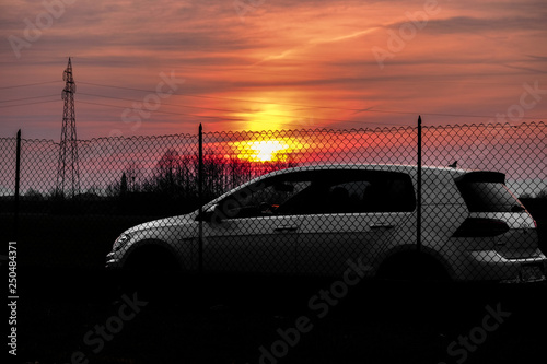 Photo  VICENZA, ITALY - January 28, 2019: White hatchback car VW Golf park behind a metal net with the sunshine in a background