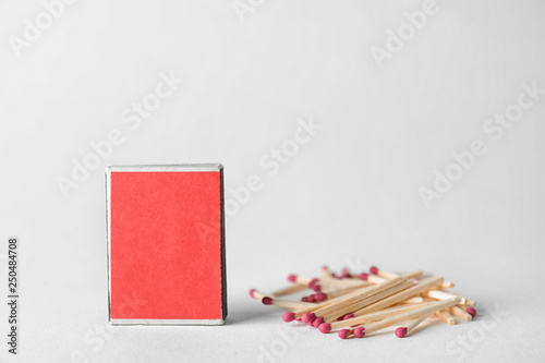 Fotografie, Obraz  Cardboard box and matches on light background. Space for design