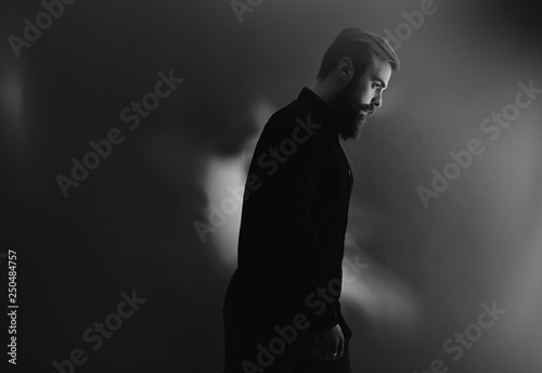 Fotografie, Obraz  Black and white photo of a stylish man with a beard dressed in the black shirt s