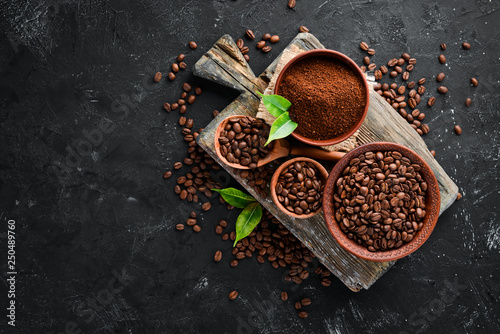 Obraz Ground coffee and coffee beans. Assortment of coffee varieties on a black background. Top view. Free space for your text. - fototapety do salonu