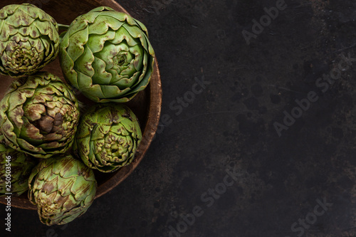 Photo Close up photo of fresh artichoke in the old wooden bowl
