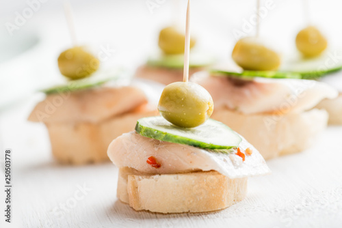 Fényképezés  canape with a piece of fish and olive on a light background