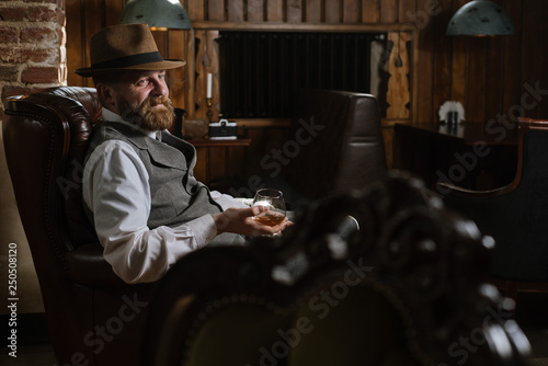Fotografie, Obraz  A man in hat wearing vintage suit holding pipe and glass of whiskey sitting on a