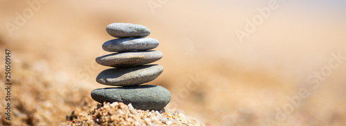 Photo Stands Stones in Sand Balance of stones on the beach, sunny day