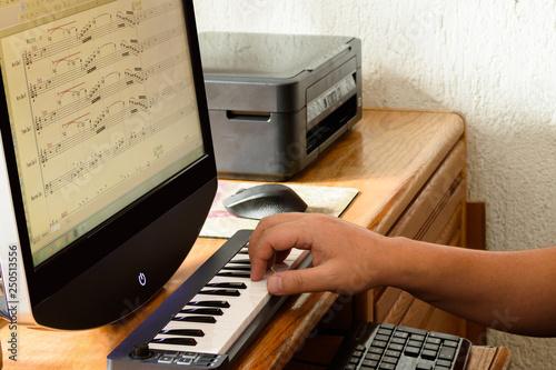 Fotografía  Compositor trabajando en computadora con teclado musical