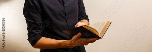Missionary man holds his bible with interlocked fingers to pray. Canvas Print