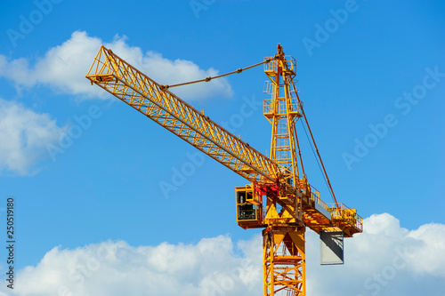 Canvas Print Yellow construction tower crane, heavy industry, blue sky and white clouds on ba