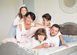 Photo of four members adopted family lying floor toothy smiling fluffy carpet cozy apartments