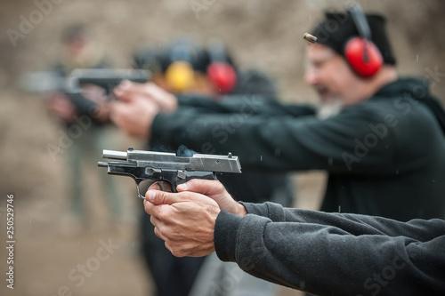 Tela Group of civilian practice gun shooting on outdoor shooting range