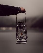 Man's Hand Holding Lantern By Lake