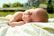 Close Up Of Shirtless Baby Girl Sleeping On Blanket In Yard