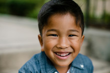 Close-up Portrait Of Cute Happy Boy Sitting On Steps At Balboa Park