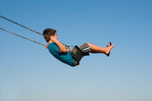 Side View Of Carefree Boy Swinging On Swing Against Clear Blue Sky At Playground