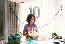 Happy Boy Looking Away While Standing By Birthday Cake Against Window At Home