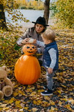 Mother With Cute Son Decorating Jack O Lantern In Park During Autumn