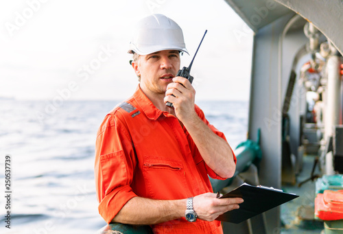 Fotografia Marine Deck Officer or Chief mate on deck of offshore vessel or ship , wearing PPE personal protective equipment - helmet, coverall