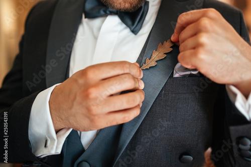 Billede på lærred Unrecognizable groom pinning decoration on lapel of his suit before wedding ceremony