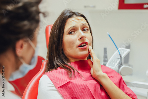 Fotografija  Close-up portrait of a sad young girl with a painful tooth, a doctor in office chairs, an isolated dentist office background clinic
