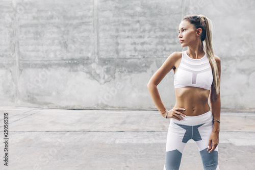 Fotografía Fitness sport model in fashion sportswear posing over gray wall