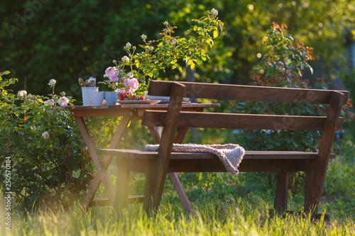 Fototapety, obrazy: Morning tea in the garden. Fresh roses on wooden table, sunny day, natural ligh