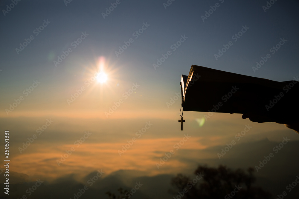 Fototapety, obrazy: Silhouette of human hand holding bible and cross, the background is the sunrise., Concept for Christian, Christianity, Catholic religion, divine, heavenly, celestial or god.